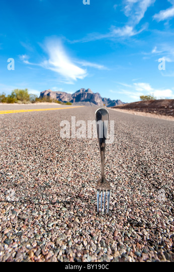 A fork in the road infers a decision point in ones life. - Stock Image