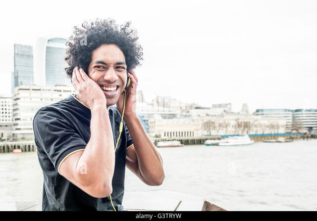 A young man listening to music via headphones on the South Bank in London. - Stock Image