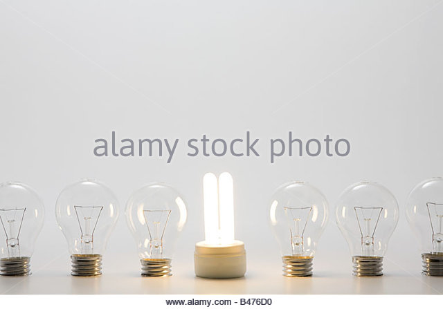 An energy saving lightbulb and ordinary lightbulbs - Stock Image