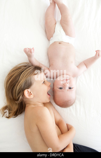 Sister kissing her younger sibling - Stock Image