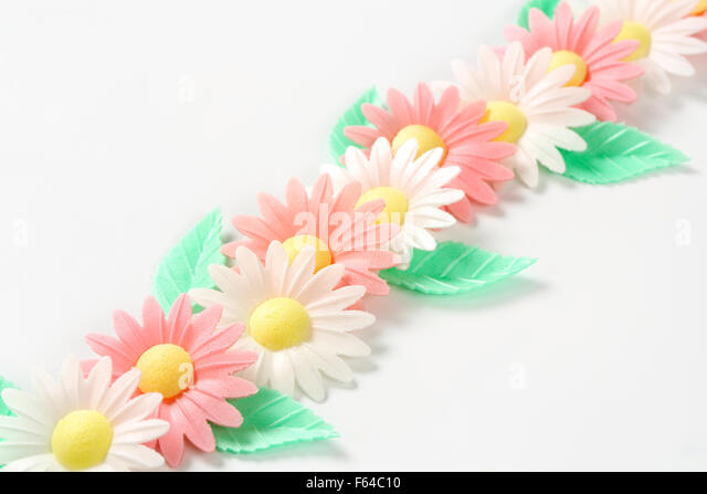 sugar flowers - eatable cake decoration on white background - Stock Image