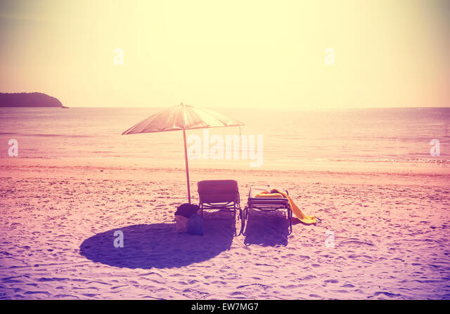 Vintage instagram stylized deckchairs and umbrella at sunset. Concept for holidays and relaxation. - Stock-Bilder