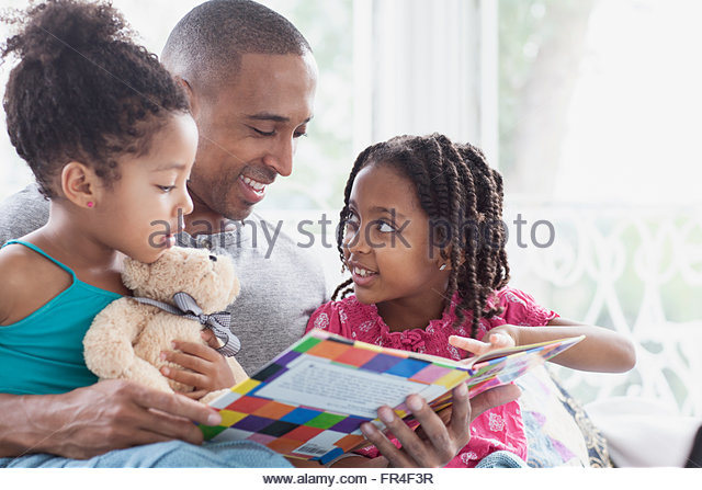 father reading to his two young daughters - Stock-Bilder
