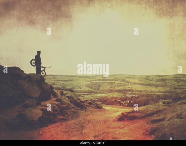 Man with bike on Cow and Calf rocks in Ilkley, West Yorkshire - Stock Image