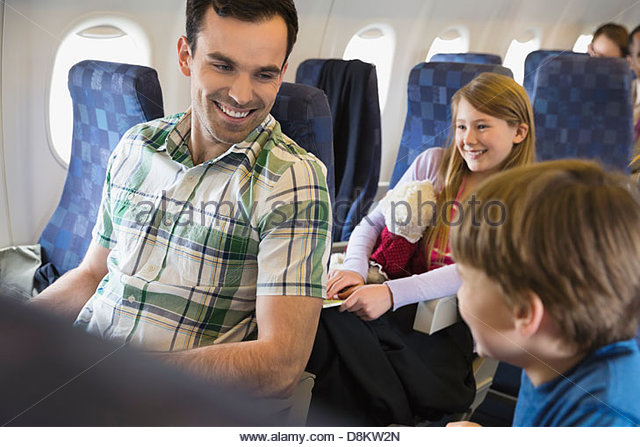 Father with children traveling in airplane - Stock-Bilder