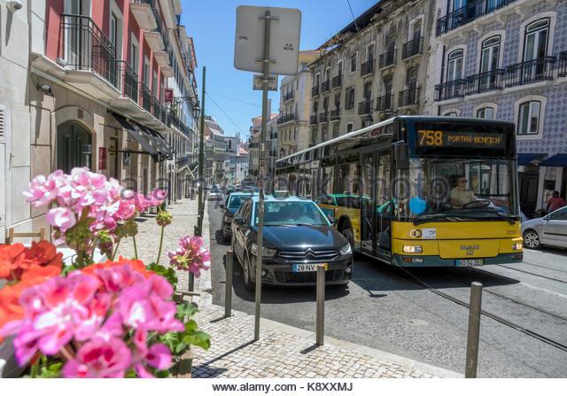 Portugal Lisbon Bairro Alto Rua da Misericordia street scene flowers geraniums taxi stand bus city skyline - Stock Image