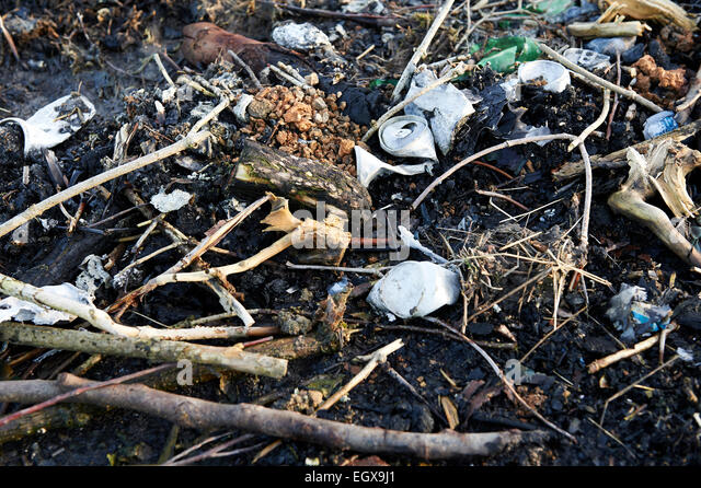 Burnt fly-tipped waste on agricultural land. - Stock Image