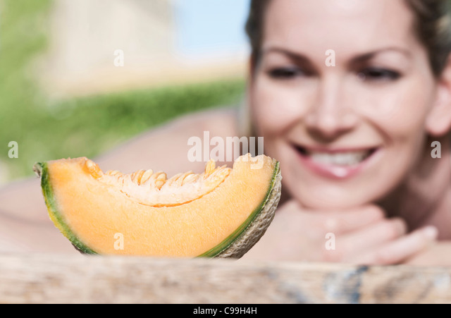 Italy, Tuscany, Magliano, Slice of honey melon in front of young woman, smiling - Stock Image
