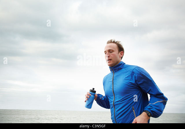 Man running by the sea on cloudy day - Stock Image