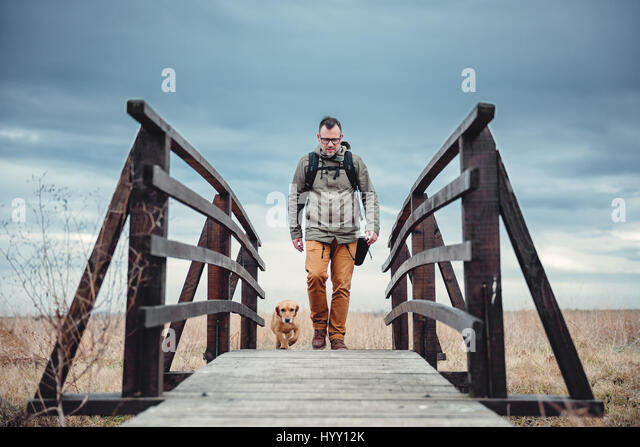Hiker and dog crossing wooden bridge on the cloudy day - Stock-Bilder