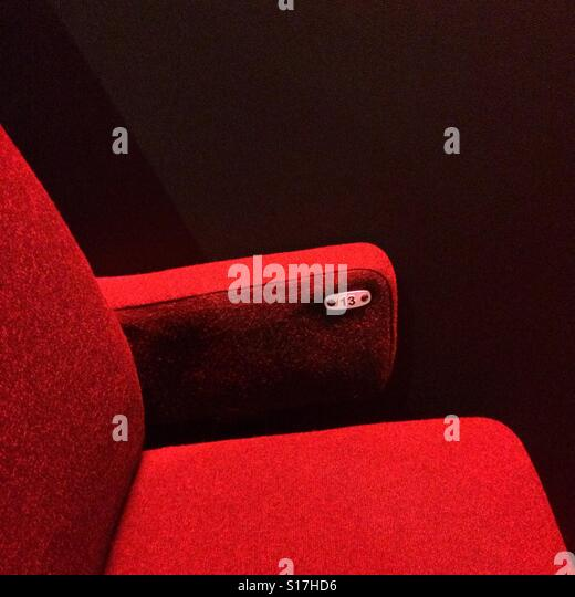 A red theatre chair numbered 13 - Stock Image