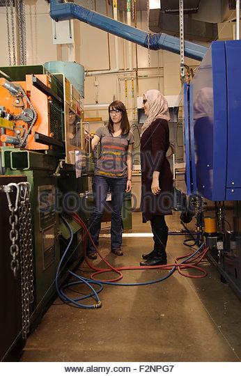 Women working on machinery in workshop - Stock-Bilder