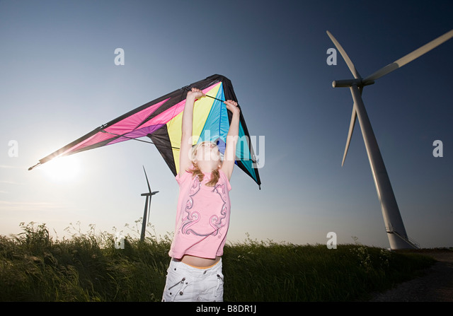 Girl with kite by wind farm - Stock Image