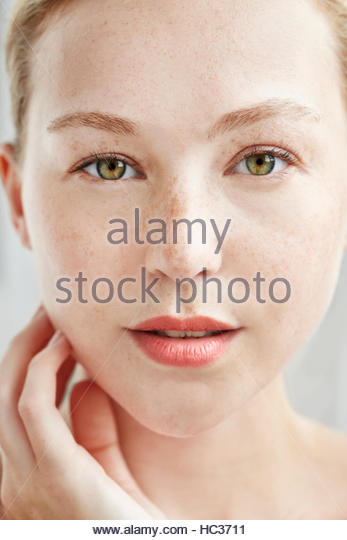 Portrait of young woman touching face, close up. - Stock Image