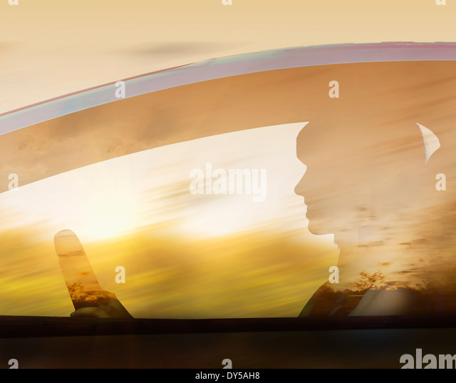 Silhouette of woman driving car - Stock Image
