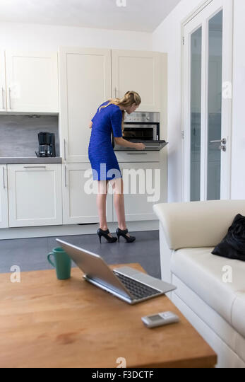 Woman in blue dress cooking at home - Stock Image