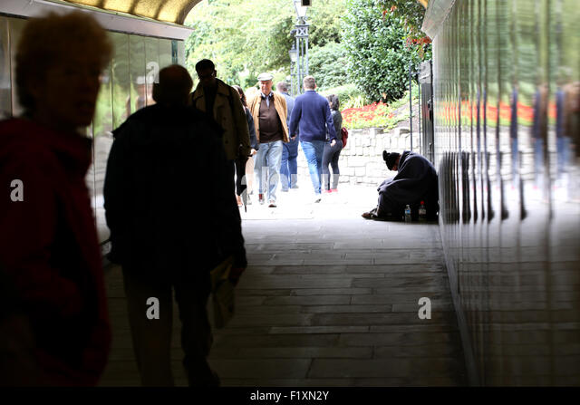 A homeless male sat begging but looking down and out in an underpass in central London as people pass by on a busy - Stock Image