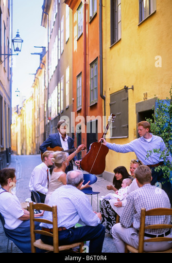 SWEDEN STOCKHOLM THE OLD TOWN NEIGHBOURS HAVING A PARTY IN NARROW OLD TOWN STREET - Stock Image