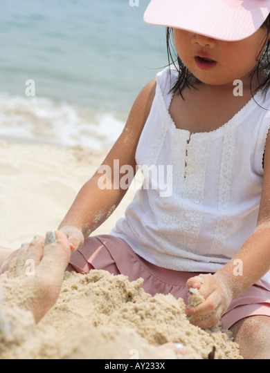 Close-up of a girl making a sand castle on the beach - Stock Image