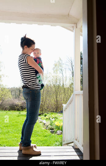 Sweden, Ostergotland, Vikbolandet, Woman carrying baby boy (6-11 months) - Stock Image