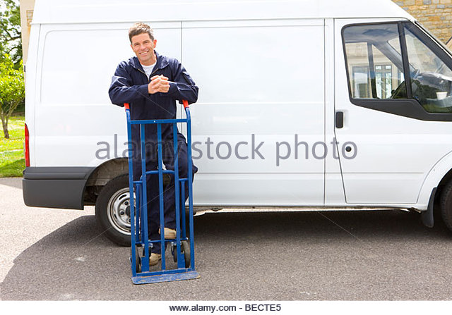 Smiling man in coveralls leaning on hand truck near work van - Stock Image