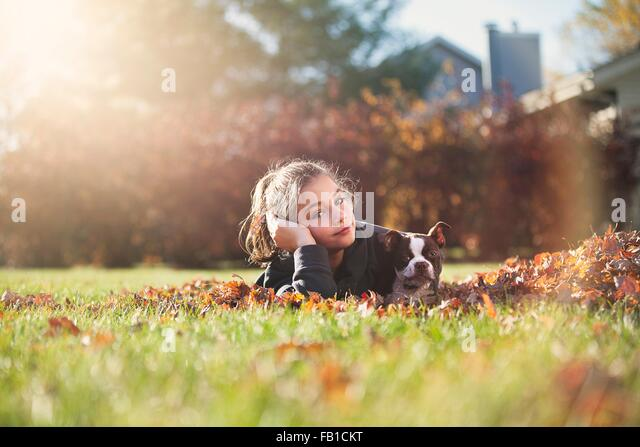 Girl with Boston terrier puppy lying on front on Autumn leaf covered grass, resting on elbow looking at camera - Stock Image