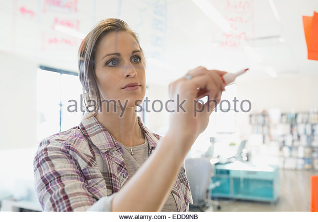 Businesswoman writing on glass - Stock Image