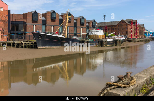 Obsolete ship beached on mud bank of river Hull with view of quayside buildings and the river in Hull, Humberside, - Stock Image
