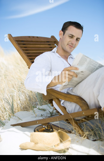 Young man sitting in deck chair on beach, reading newspaper - Stock Image