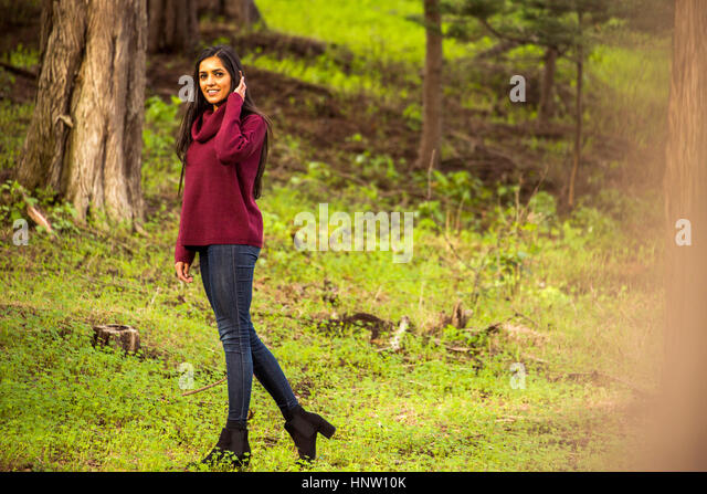 Smiling Indian woman posing in forest - Stock-Bilder