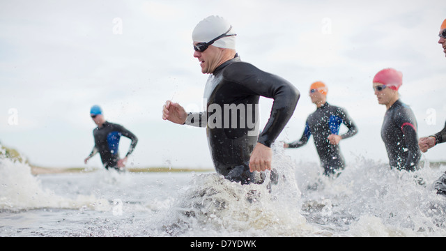 Triathletes in wetsuits running in waves - Stock Image