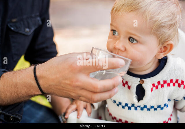 Midsection of father feeding water to baby girl in park - Stock Image
