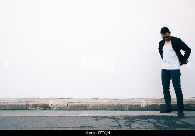 Young Man Looking Down Standing Against White Wall - Stock Image