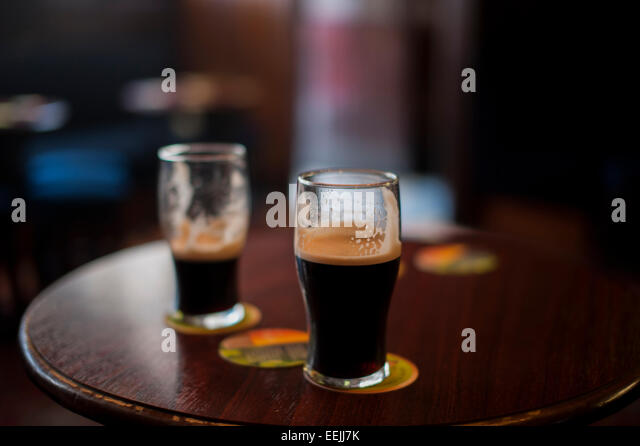 Two half full glasses of Guiness on a pub table, Dublin, Republic of Ireland - Stock Image