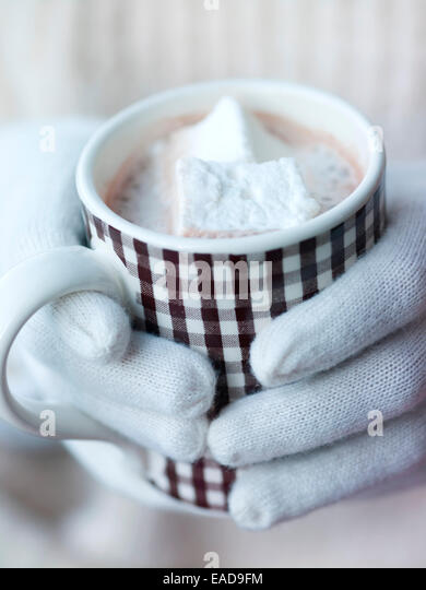 mittened hands holding mug of hot cocoa with marshmallows - Stock Image
