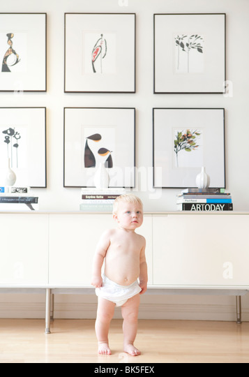 Baby in diaper in modern home - Stock Image