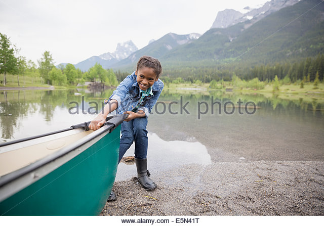 Girl pulling canoe into lake - Stock Image