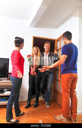 France,  couple receiving friends arriving with gifts - Stock Image