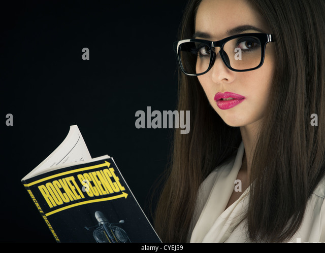 Woman wearing glasses studying Rocket Science - Stock Image