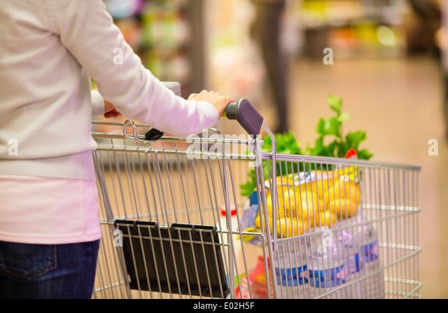 Female trolley supermarket shop background - Stock Image
