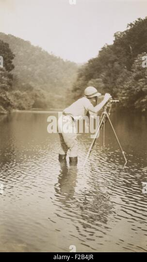 Marvin Breckinridge Patterson taking a photograph while standing in a river, 1935. She was a widely published photographer - Stock-Bilder