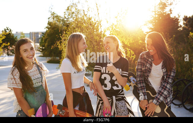 Four girls hanging out while talking and laughing - Stock Image