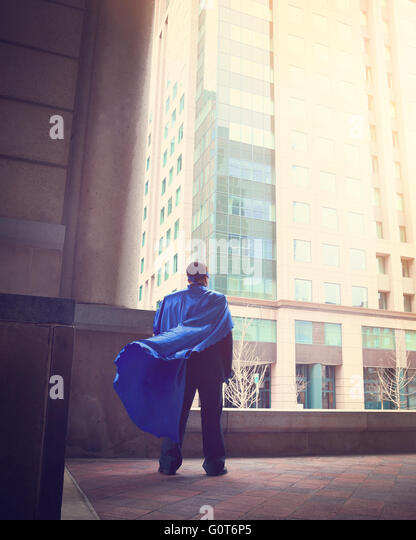 A business man wearing a super cape is standing in a city for a success, strength or power career concept. - Stock Image