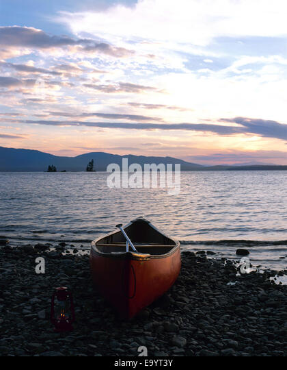 canoe by Maine lake at sunset - Stock Image
