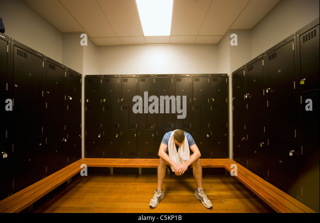 A man sitting in locker room at a gym with a towel round his neck, looking down and looking exhausted - Stock Image