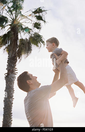 Man standing by a palm tree, playing with his young son, lifting him into the air. - Stock Image