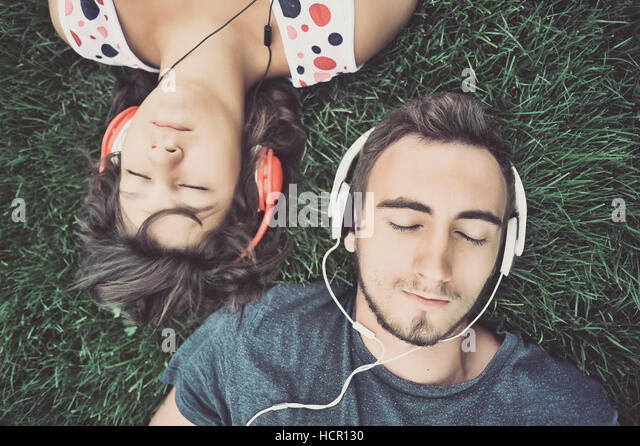 Couple listening to music on headphones - Stock Image