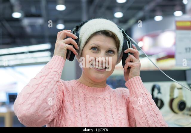 woman chooses Headphones in shop - Stock Image