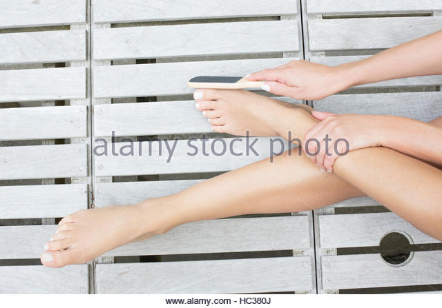 Woman giving herself pedicure on patio. - Stock Image