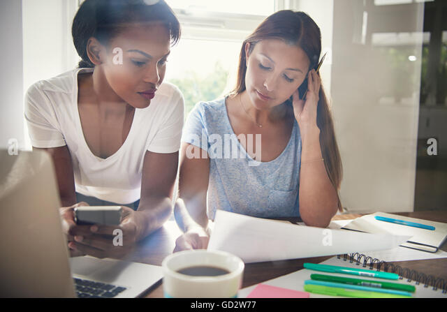 Two successful multiracial female business colleagues checking a spreadsheet together in the office reading the - Stock Image